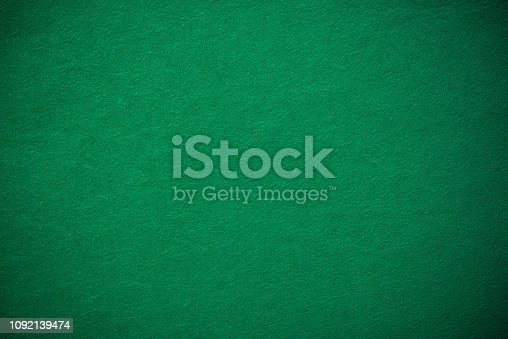 Empty green casino poker table cloth with spotlight.