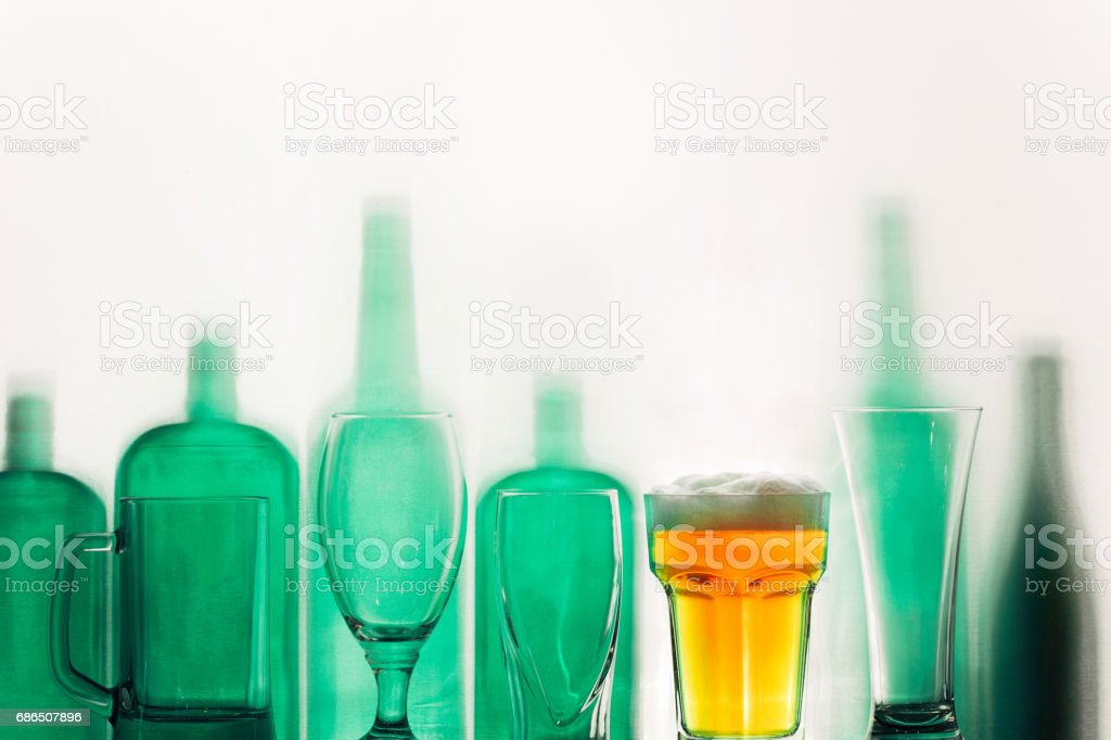 Empty green glass bottles and a glass of beer stand in row Drink Concept royalty free stockfoto