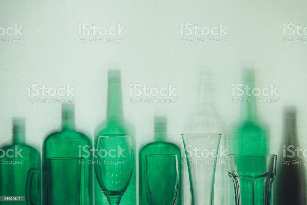 Empty green glass bottles and beer glasses stand in row Drink Concept stock photo