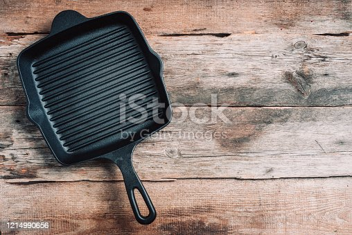 Empty grill iron pan on wooden background. Top view. Copy space. Healthy, clean food and eating concept. Zero waste. Cooking frame.