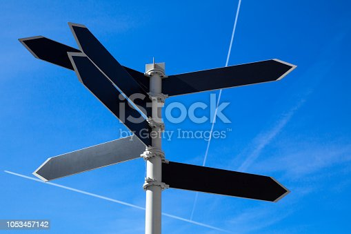 Empty guidepost with arrow shaped labels over blue sky background