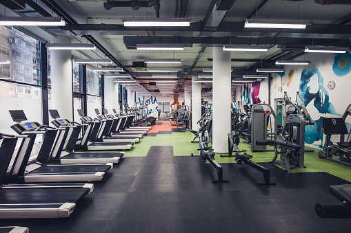 Large group of exercise machines in an empty gym.