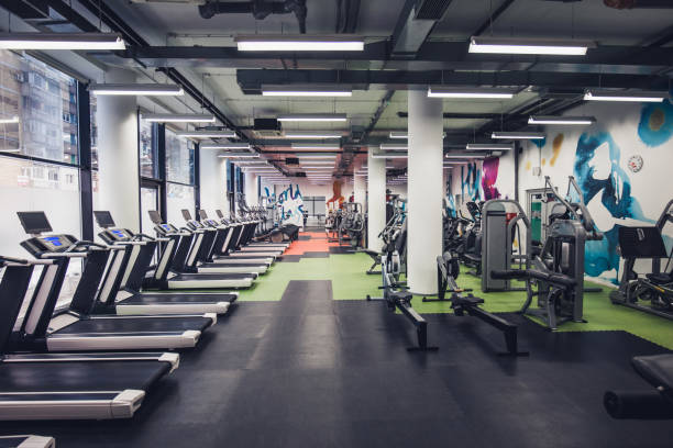 Empty gym! Large group of exercise machines in an empty gym. health club stock pictures, royalty-free photos & images