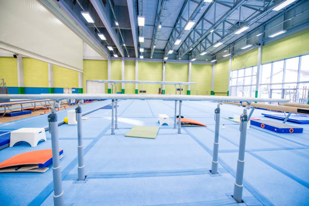 empty gymnastics gym - uneven parallel bars stock photos and pictures