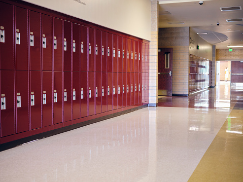 An empty hallway with lockers in a high school.