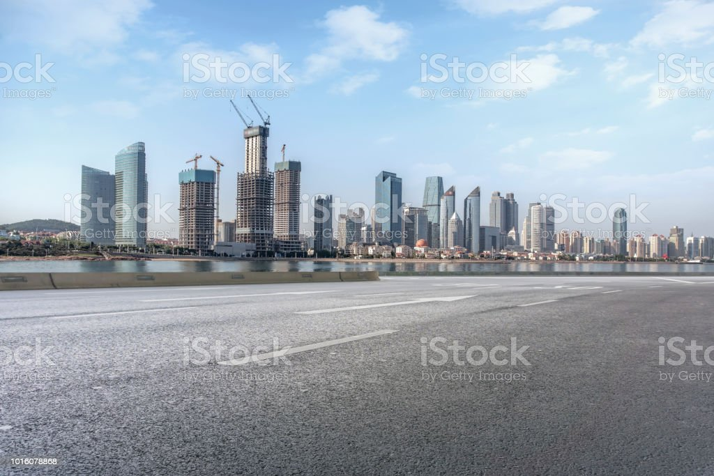 Empty highway asphalt road with Qingdao urban architecture landscape...
