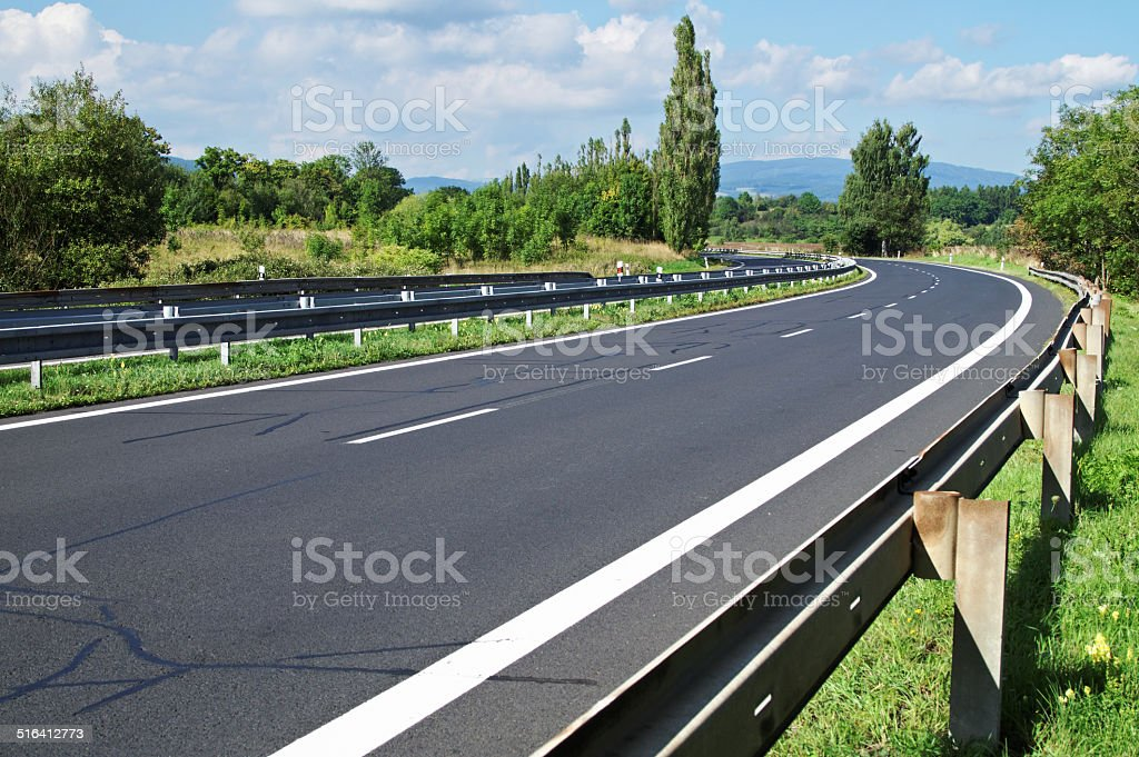 Empty highway passing landscape trees stock photo