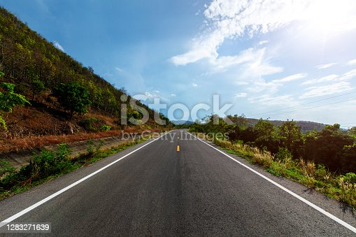 istock Empty highway road through the green field and clouds on blue sky in summer day. 1283271639