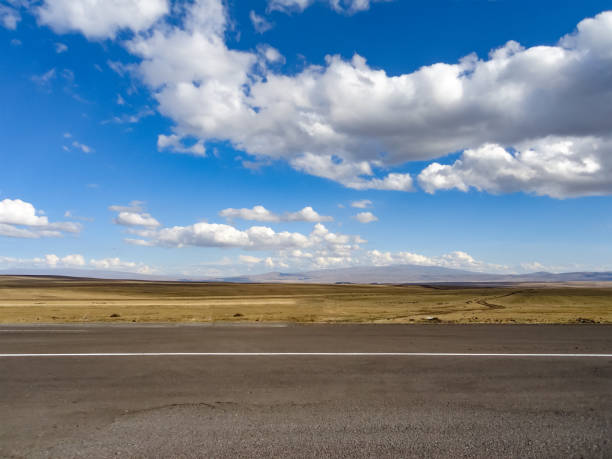 Empty highway with steppe behind and blue cloudy sky stock photo