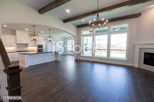 Empty living area and kitchen inside of a new modern home. The sun shines through lare windows in the living area.