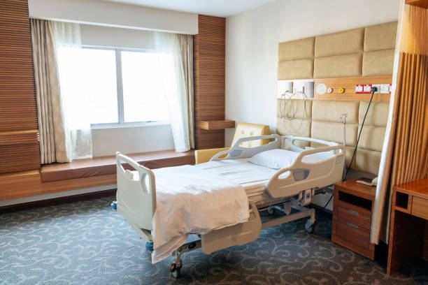 Empty hospital bed on ward Hospital room with ready made bed and bedclothes, window to one side and carpeted floor hospital ward stock pictures, royalty-free photos & images