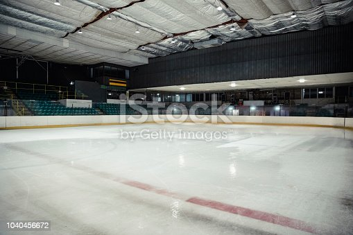 Wide angle view of an interior of an empty ice rink. There are no people in the seats or on the ice.