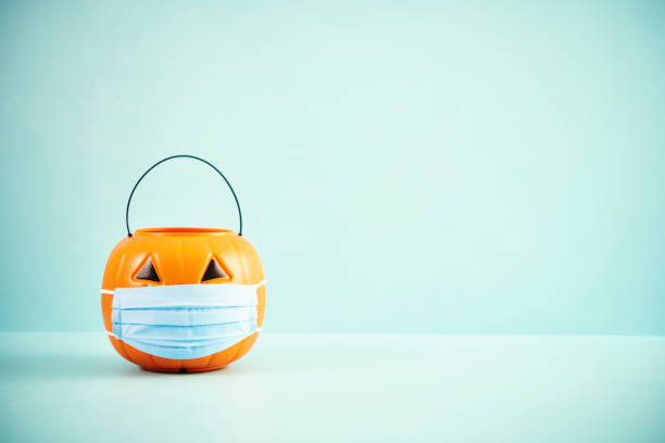 Empty Jack O'Lantern Trick or Treat Bucket with Face Mask Halloween Background stock photo