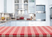 Empty kitchen countertop covered with red and white checkered tablecloth with blurred modern kitchen at background. Predominant colors are white and red. Very suitable for product montage.