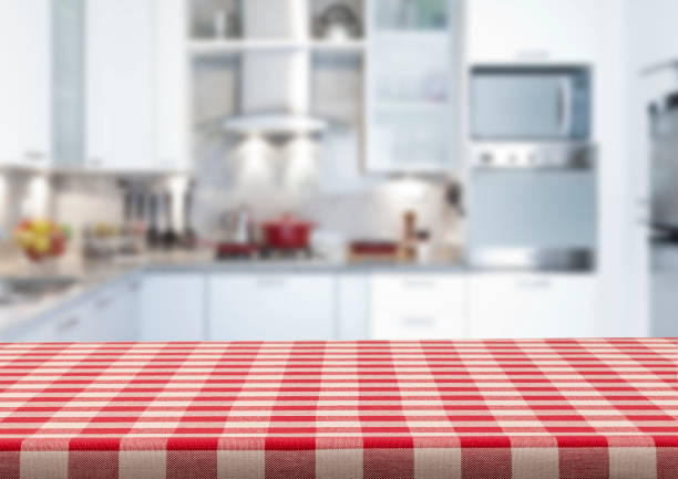 Empty kitchen countertop covered with red and white checkered tablecloth Empty kitchen countertop covered with red and white checkered tablecloth with blurred modern kitchen at background. Predominant colors are white and red. Very suitable for product montage. red cloth stock pictures, royalty-free photos & images