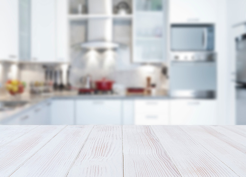 Empty kitchen countertop with defocused modern kitchen background. Highly suitable for product montage