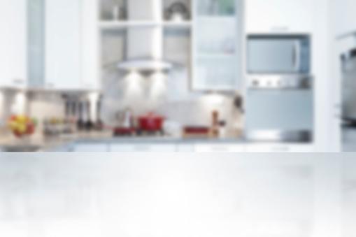 Empty kitchen countertop with defocused modern kitchen background