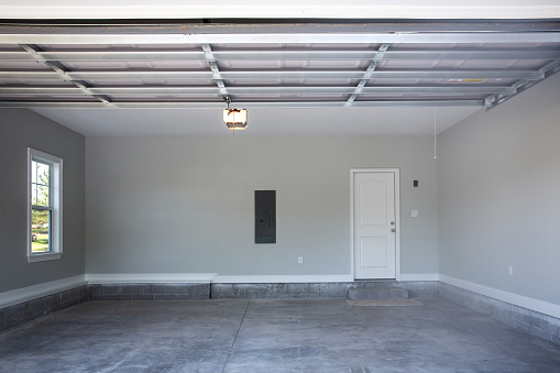 Empty large two-car garage with cement floors and a door to the inside as well as a garage door opener painted in a neutral gray color