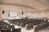 istock Empty lecture hall with several rows of seats and a screen 186826741