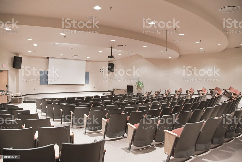 Empty lecture hall with several rows of seats and a screen stock photo