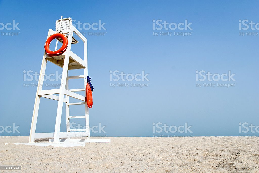 Empty Lifeguard Chair on the beach Empty white lifeguard chair on an empty beach with  orange life buoys hanging on the side.The chair stands against a clear blue sky in the sand. Abundance Stock Photo