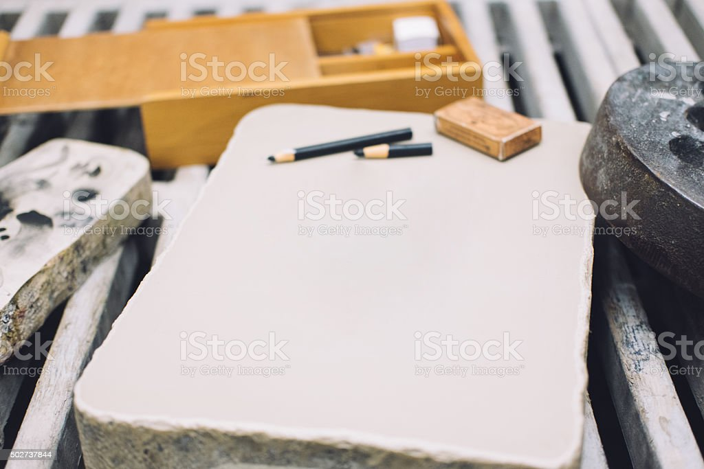 Empty lithographic stone woth crayons stock photo