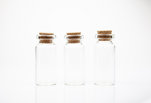 istock Empty little bottles with cork stopper on white background 1085043374