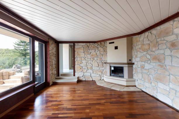 Leeres Wohnzimmer mit Parkett, Kamin, Fenstern und Fels an den Wänden – Foto