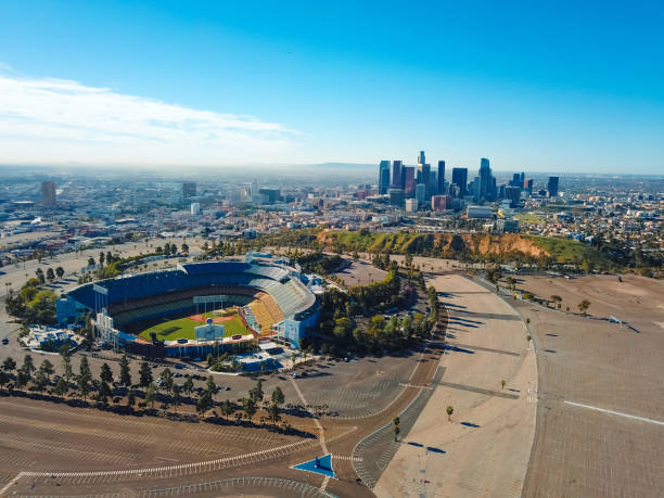 Empty Los Angeles Dodgers baseball stadium and Los Angeles skyline Los Angeles, California, USA - February 16, 2018: Aerial view from helicopter of Los Angeles Dodger Stadium in Elysian Park, with the skyscraper skyline of Los Angeles in the smoggy background distance. The Stadium is just north of downtown Los Angeles and is the home of the Los Angeles Dodger major league baseball team. The stadium in this photo is empty at a time when no game is being played. major league baseball stock pictures, royalty-free photos & images