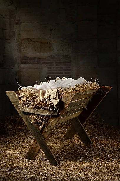 Empty Manger in Stable Manger filled with hay in stable with baby soft cloths on top trough stock pictures, royalty-free photos & images