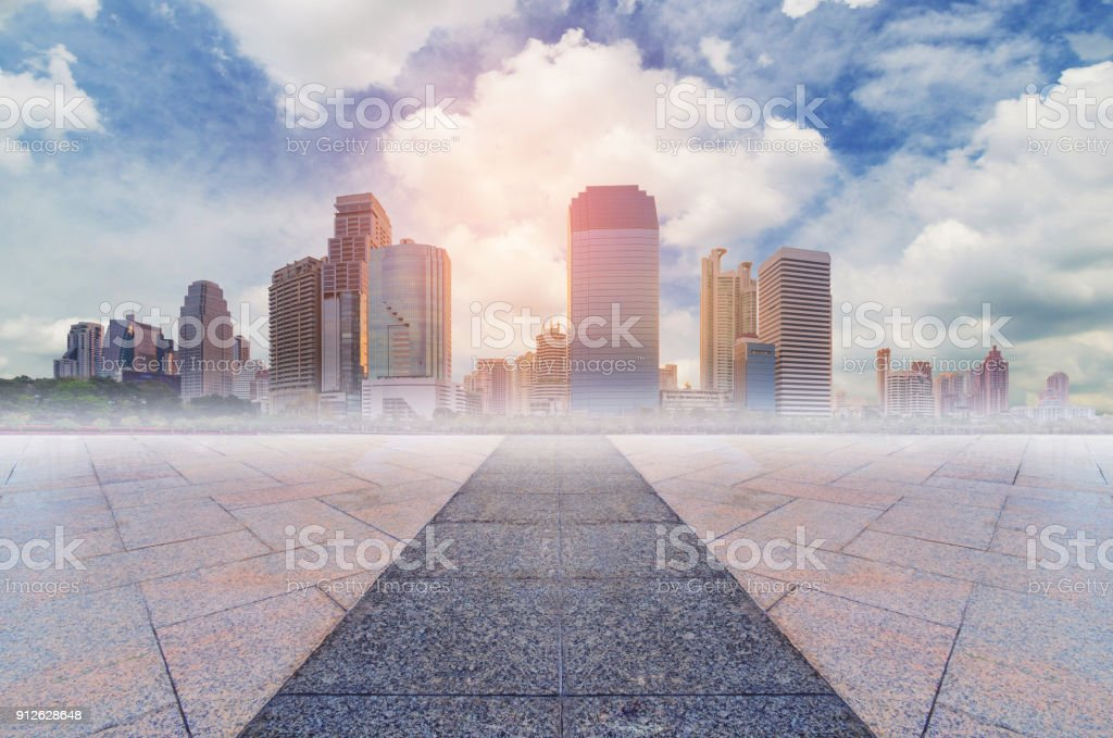 empty marble floor with the lead line to modern building skyline in the metropolis city with blue sky and cloud. stock photo