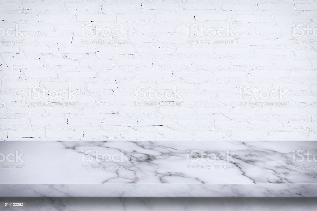 Empty marble table with white brick wall background.