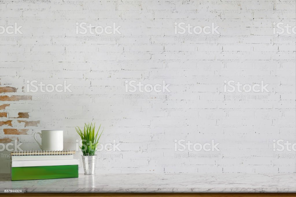 Empty marble top table with books, coffee mug and houseplant. Copy space for products display montage. stock photo