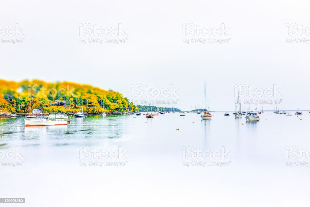 Empty marina harbor in small village in Maine during rain with boats in autumn stock photo