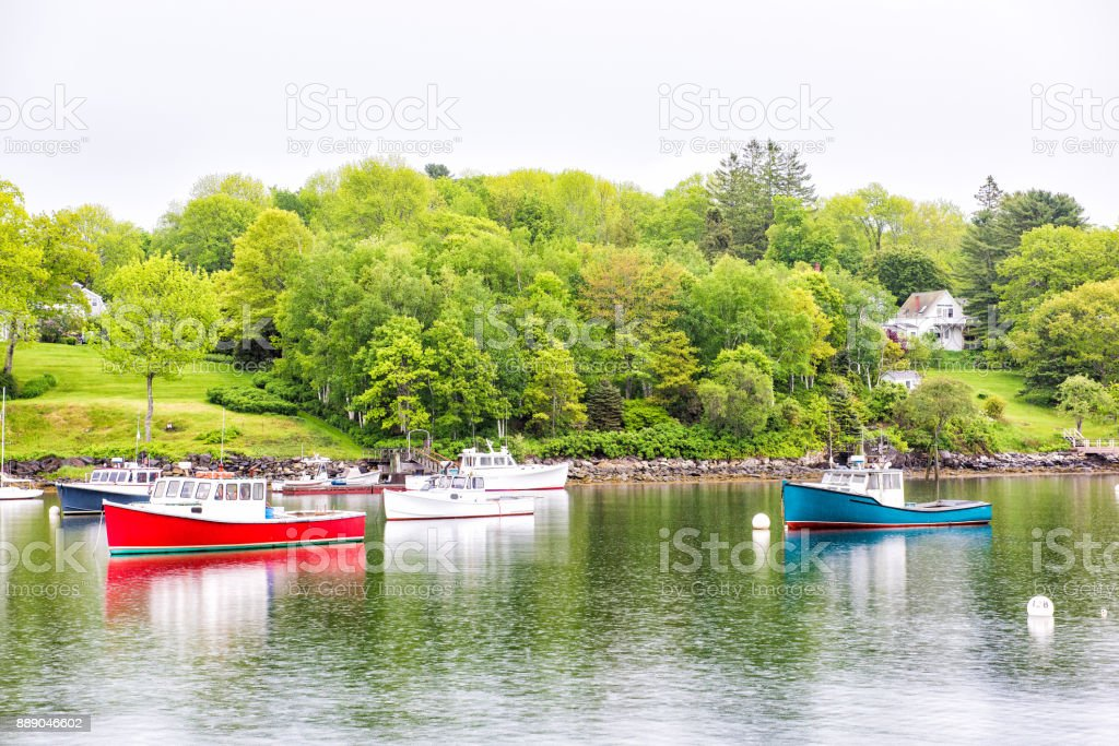 Empty marina harbor in small village in Maine during rain with boats stock photo