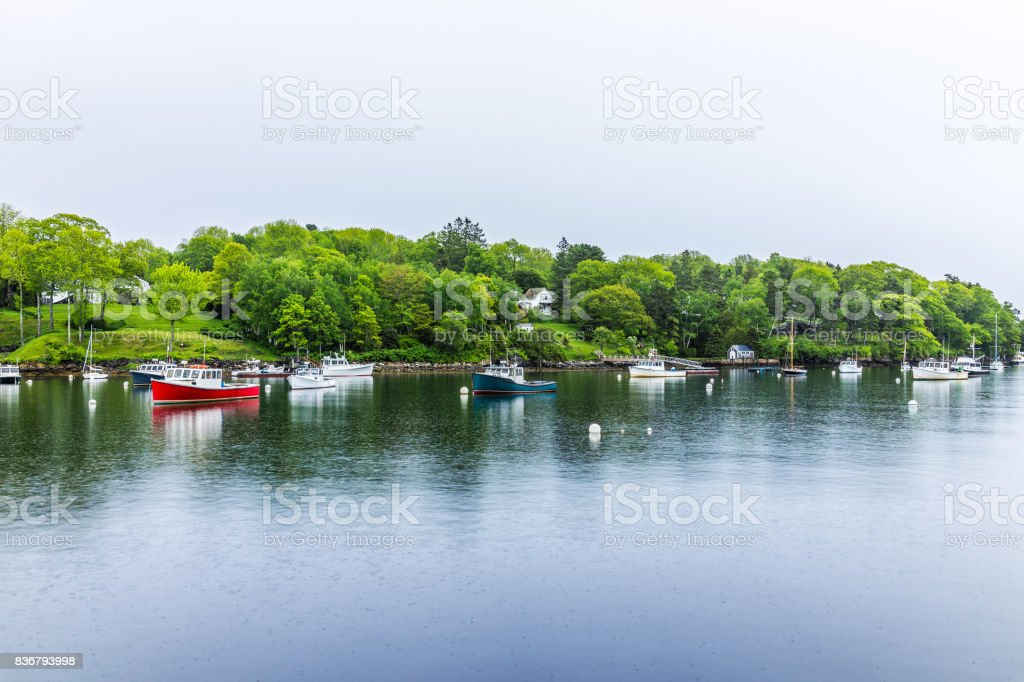 Empty marina harbor in small village in Rockport, Maine during rain with boats stock photo