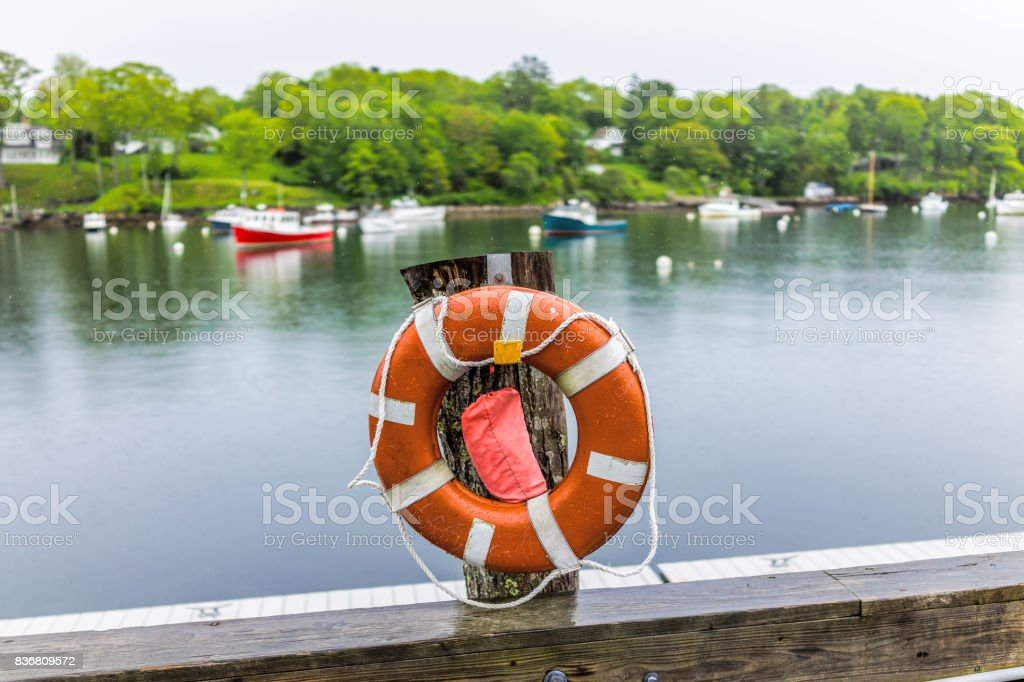 Empty marina harbor in small village of Rockport, Maine during rain with boats and life buoy stock photo