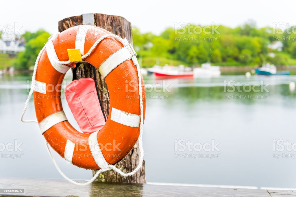 Empty marina harbor in small village of Rockport, Maine during rain with boats and orange life buoy or lifebuoy stock photo