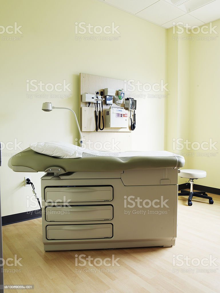 Empty medical exam room with examination table and instruments on wall royalty-free 스톡 사진