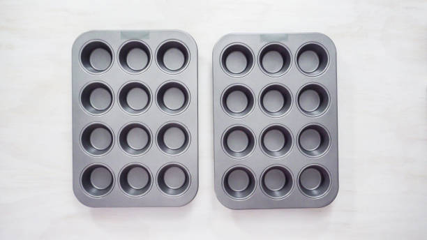 Empty metal cupcake pan on the table. Flat lay. Step by step. Empty metal cupcake pan on the table. muffin tin stock pictures, royalty-free photos & images