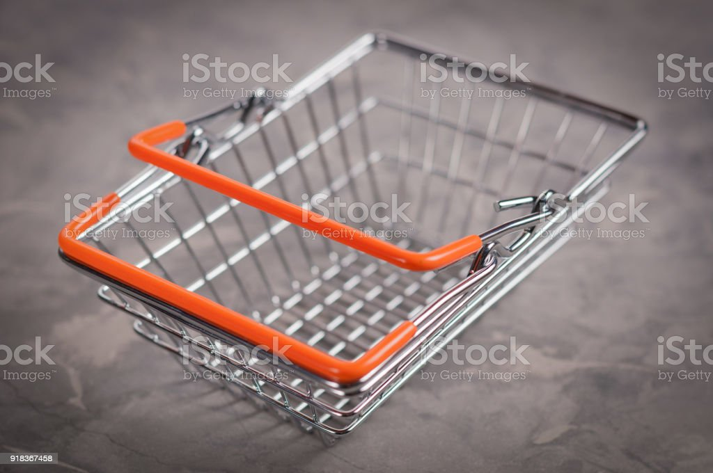 Empty metal glossy market basket with orange handles on cracked old...