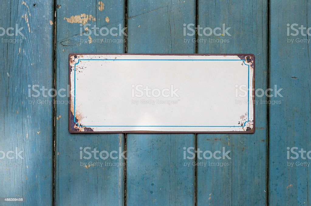 Empty metal sign in front of a wooden wall stock photo