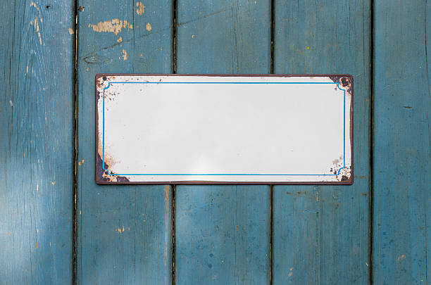 empty metal sign in front of a wooden wall - enamel stock photos and pictures