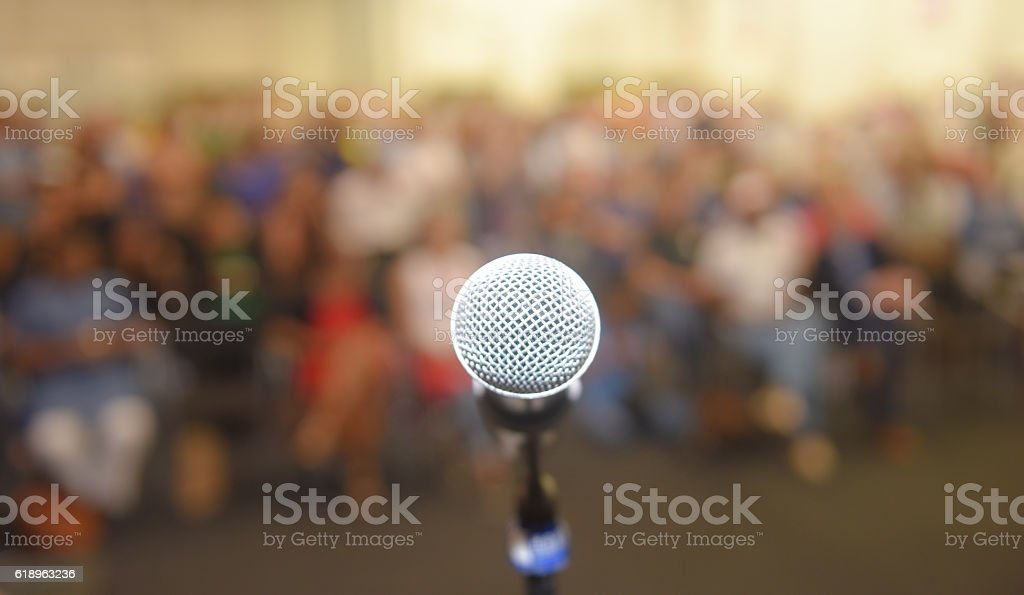 Empty microphone in front of a crown of people stock photo