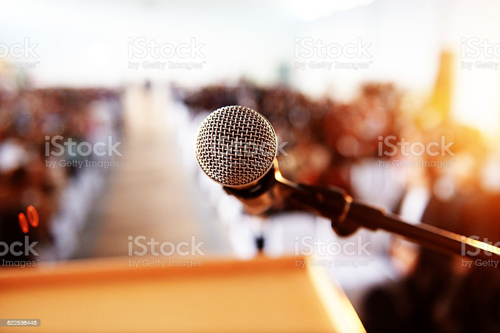 Empty microphone in front of packed hall stock photo