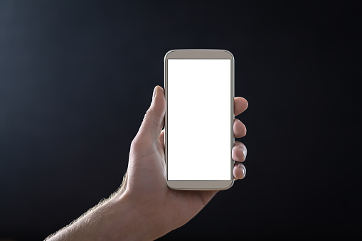 Empty mobile phone screen with dark black background in shadow at night. Hand holding smartphone with blank white display and copy space. Man showing cellphone straight to camera.