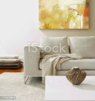 Empty modern living room with white rug and a modern vase on coffee table.  Square composition.