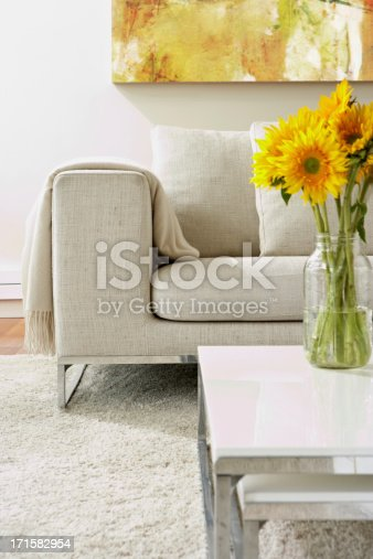 Empty modern living room with white rug and a vase with sunflowers arrangement on a coffee table.  Vertical composition.