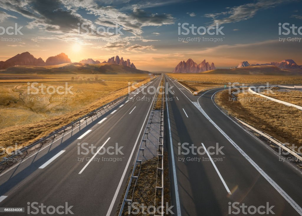 Empty motorway through vastness at idyllic sunset royalty-free stock photo