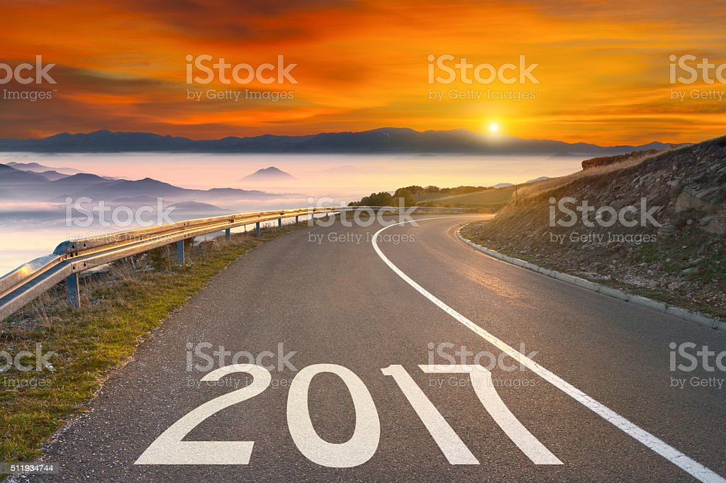 Empty mountain road to upcoming 2017 at sunset stock photo